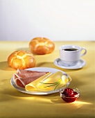 Breakfast of cheese, ham, jam, rolls and coffee
