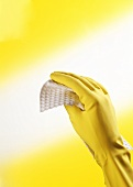 Hand in yellow rubber glove holding cleaning cloth