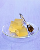 Three cubes of apple jelly on glass plate with spoon