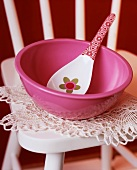 Pink bowl with spoon on crocheted cover