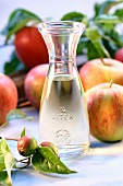 Cider vinegar in carafe, surrounded by fresh apples