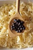 Juniper berries on wooden spoon over sauerkraut