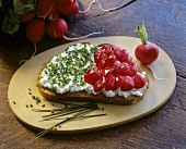 Bread topped with soft cheese, chives and radishes