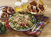Hearty snack with sausage salad, pretzels and beer
