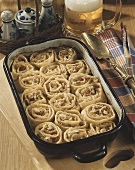 Pasta rolls with sauerkraut and bacon filling in baking dish
