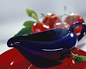 Warm sauce in blue sauceboat in front of red cherries