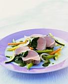 Poached veal fillet on julienne vegetables with salsa verde