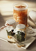 Tomato sugo and bottled fresh herbs in jars