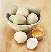 Pheasant's eggs in green bowl, one broken open