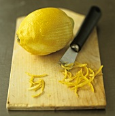 Lemon, lemon zest and zester on chopping board