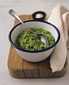 Pea puree in dish with spoon