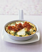 Cheese omelette with spinach and ham in frying pan