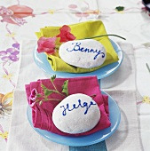 Plates with fabric napkins, flowers and painted stones