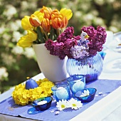 Flower and candle decoration for Easter table in open air