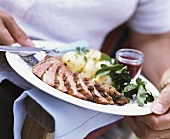 Person holding plate of roast beef and parsley potatoes