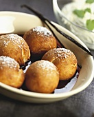 Fried dough balls with icing sugar in red wine sauce