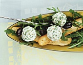Fresh cheese balls with rocket, with olives and white bread