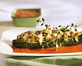 Stuffed courgettes with cheese topping in tomato sauce