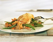 Chicken leg in strudel pastry with mangetout peas and carrots
