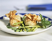 Filled strudel pastry purses with green asparagus & herb sauce