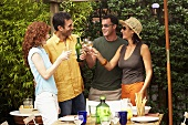 Two couples drinking white wine at barbecue