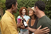 Barbecue guests giving friends red wine and flowers