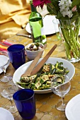 barbecued courgette strips with herbs on table in open air