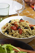 Pasta salad with dried tomatoes on table in open air