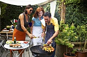 Friends barbecuing food in garden