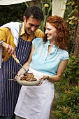 Couple serving barbecued sausages in garden