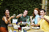 People raising wine glasses at party in garden