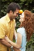 Fröhliches Paar balanciert Orange zwischen den Köpfen