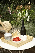 Champagne bottle, strawberries and cream on tray in open air