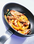 Gambas in frying pan in orange sauce