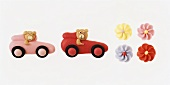 Sweet cake decorations: sugar flowers, marzipan bear in car