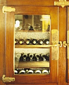 Several wine bottles in wood-panelled drinks cabinet