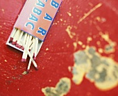 Box of matches, opened, on red table top