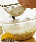 Sieving sugar onto cake mixture in bowl