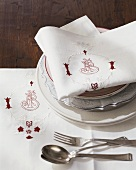 Place setting with embroidered fabric napkin