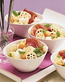 Colourful pasta salad with ham, melon and mozzarella