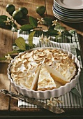 Key lime pie in baking dish, partly sliced