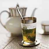 Hot peppermint tea in glass in front of teapot