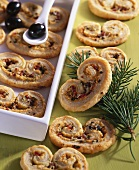 Puff pastry 'pig's ears' filled with cheese, ham and olives