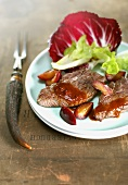 Venison escalopes with plum sauce and salad