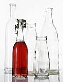 Bottle of cranberry juice and empty glass bottles