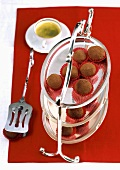 Tiramisu chocolates on tiered stand in front of coffee cup