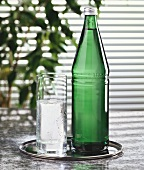 Mineral water in glass and green bottle on tray