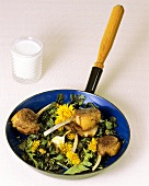 Lamb cutlets with fried dandelion leaves & flowers in frying pan