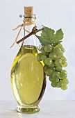 Grape seed oil in bottle with green grapes