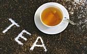 Tasse Schwarztee, umgeben von Teeblättern mit der Schrift TEA